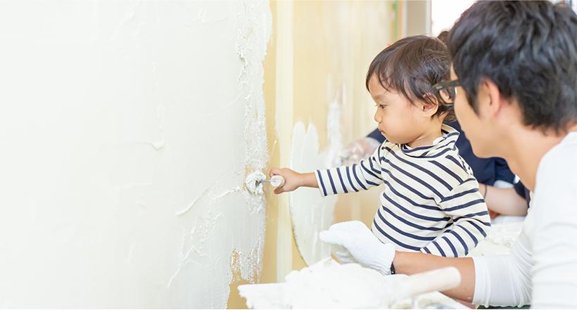 家族で漆喰を塗っている写真